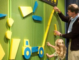 Father and daughter playing at the puzzle wall.